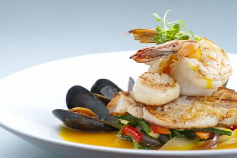 Prepared dish with shrimp atop sauteed fish, plated with steamed vegetables and mussels.