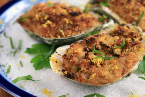 Close-up of plated baked stuffed oysters.