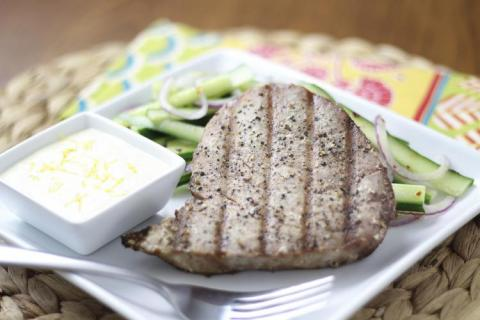Grilled tuna steak plated with dipping sauce and vegetables.
