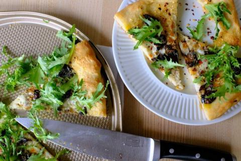 Garlic chili oil and smoked oyster pizza on baking sheet with several slices on white plate garnished with fresh greens