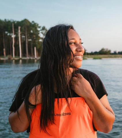 Founder of Minorities in Aquaculture, Imani Black, wearing orange waders and looking sideways over a body of water