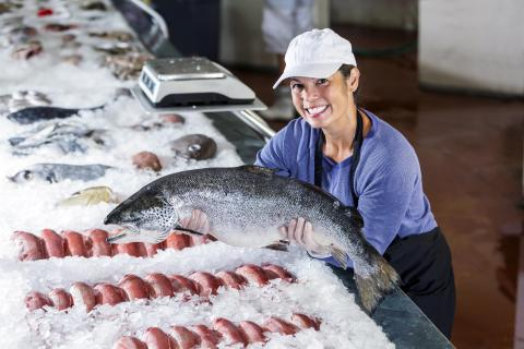 Woman in ball cap and apron hold salmon over a freezer case of seafood.