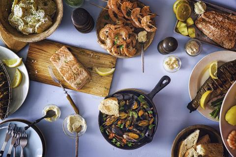 Table covered with an array of seafood dishes, including steamed mussels in an iron skillet, skewers of grilled shrimp in a bowl, baked salmon on a cedar plank, and a whole grilled fish with lemon slices.